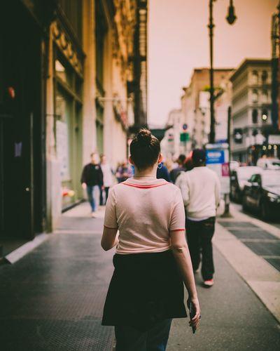 Rear view of people walking on city street