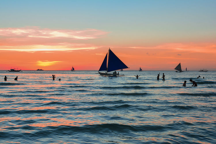 Silhouette people with sailboat in sea against orange sky