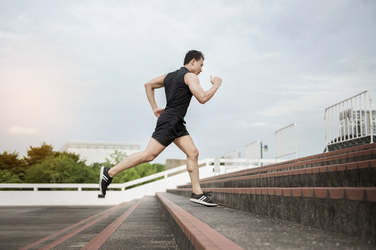 Low Angle View Of Athlete Running On Steps Against Sky