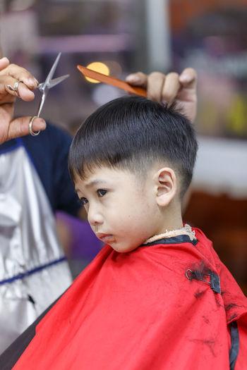 Hairdresser cutting boy hair in salon