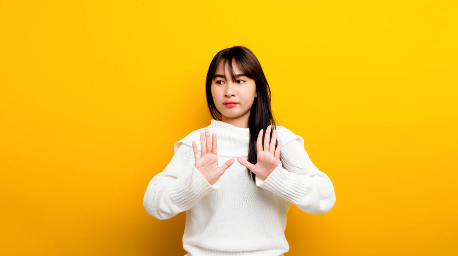 Portrait of a beautiful young woman against yellow background