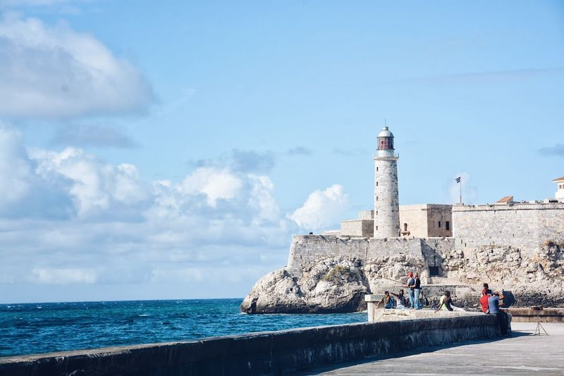 View of Morro Castle or Castillo de los Tres Reyes del Morro from el Malecón of Havana. Architecture Sea Sky Built Structure Building Exterior Cloud - Sky Water Havana Cuba Malecon Vacations Travel Destinations Malecón, La Habana Ocean Beach Life Travel Oceanview Blue Horizon Over Water Waterfront Lighthouse Been There.