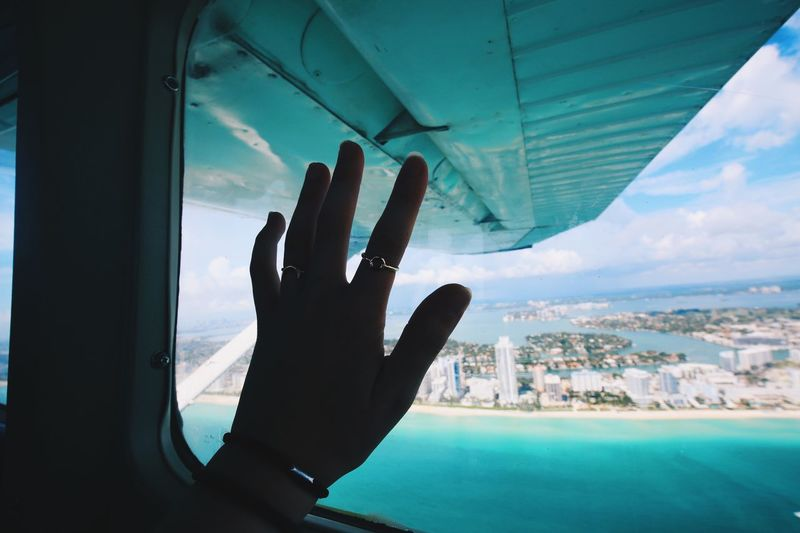 Cropped hand on window of airplane