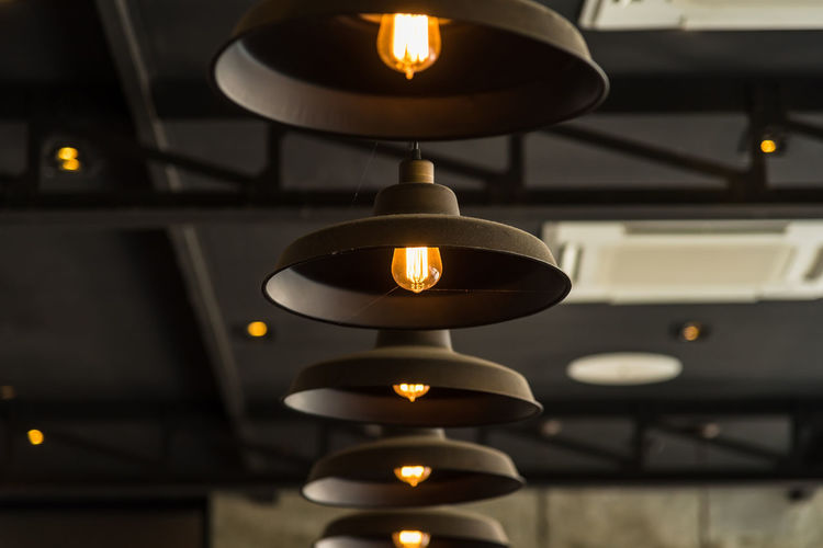 Close-up of illuminated lamp hanging on table in building