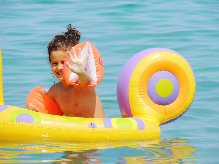 Portrait of shirtless girl with inflatable ring in sea