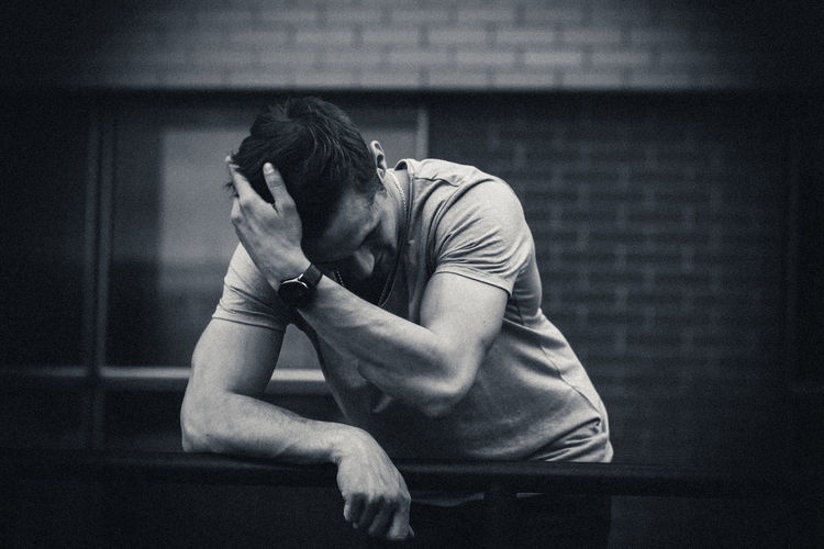 Depressed man with hand in hair standing by railing