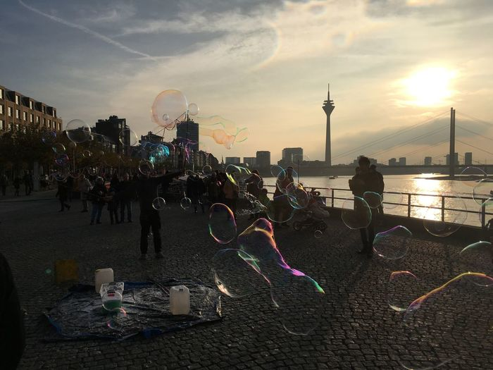 People enjoying bubbles on street with rheinturm in background during sunset