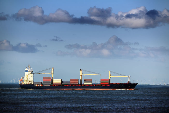 Large container ship in the north sea under a cloudy blue sky, copy space Business Goods Transportation Cargo Container Container Crane - Construction Machinery Day Freight Transportation Industry Mode Of Transport Nature Nautical Vessel No People Outdoors Sea Shipping  Shipyard Sky Transportation Water