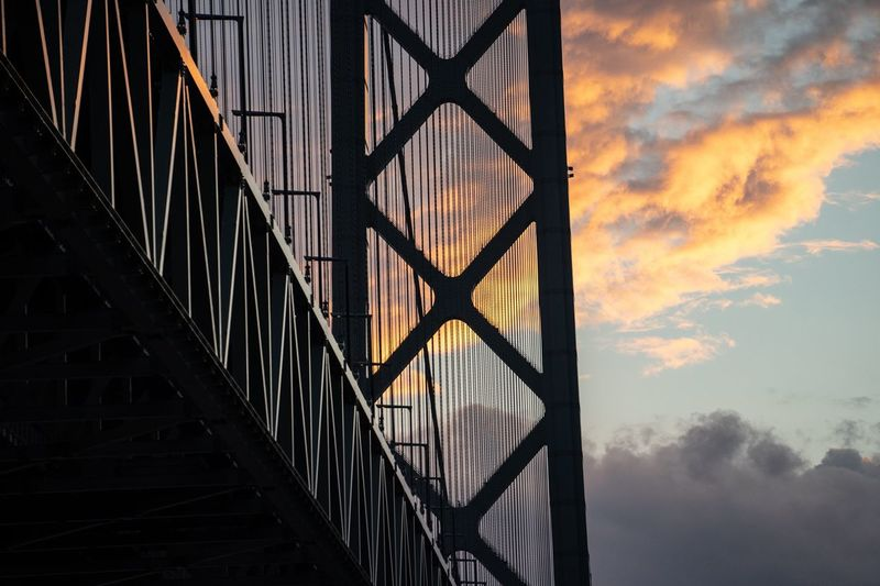 Sunset in the Akashi Kaikyo Bridge Sky Sunset Built Structure Architecture Cloud - Sky No People Nature Beauty In Nature Low Angle View Outdoors Orange Color Pattern Scenics - Nature Water Reflection Window Building Silhouette Building Exterior Sunlight
