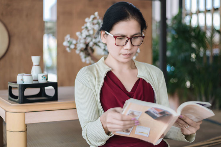 Close-Up Of Woman Reading Documents At Home