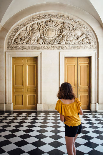 Girl Woman Women One Person Real People Renaissance Castle Standing Pattern Full Length Rear View Door Entrance Architecture Doorway Tiled Floor Palace Passageway Luxury Hotel Hallway Entryway Closed Door Hotel Suite Entry Corridor