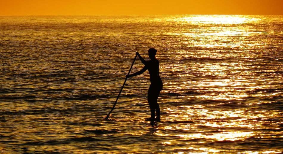 Silhouette Woman Paddleboarding In Sea During Sunset