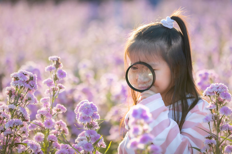 Close-up of girl with purple flowering plants