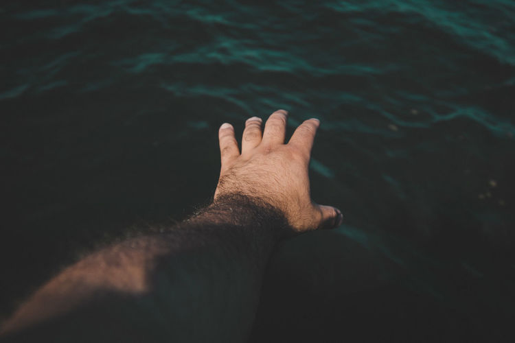 Cropped image of hand reaching towards sea