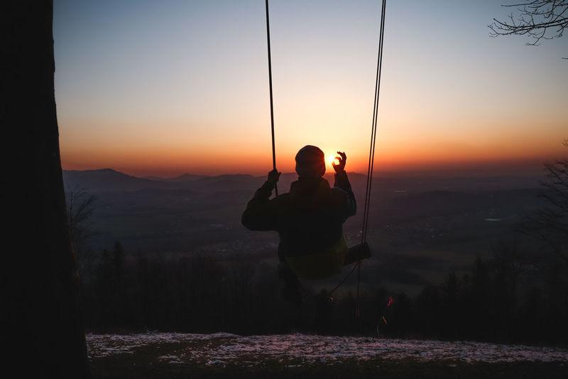 Rear view of man sitting on mountain against orange sky