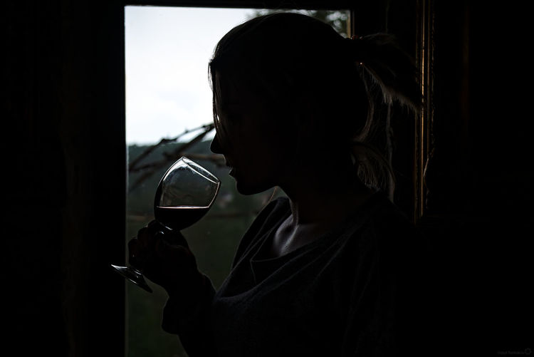 Side view of woman drinking wine