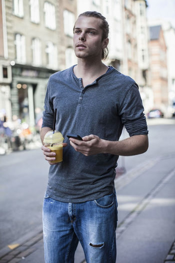 Young man drinking coffee in city