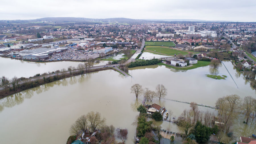 Aerial view of flooded river and cityscape against sky