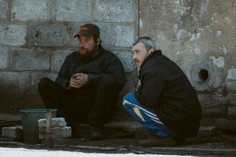 Man and woman sitting against wall in winter