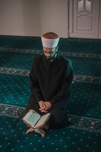 High angle of man reading koran in mosque