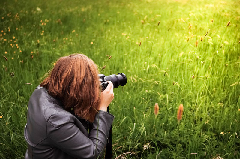 Young Woman Photographing From Camera On Grassy Field