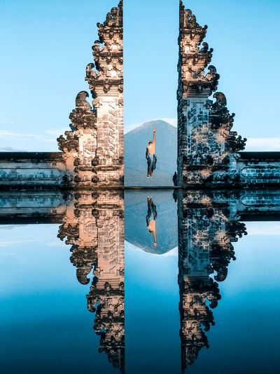 Rear view of man jumping with reflection in water at bali gate