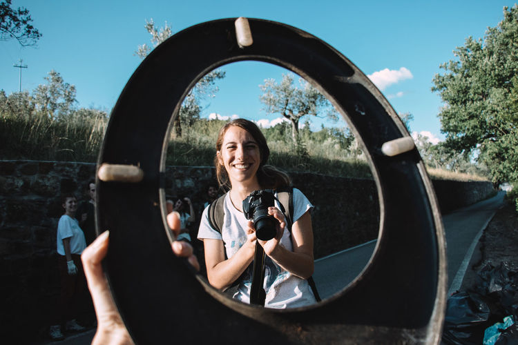 Portrait of woman photographing through camera