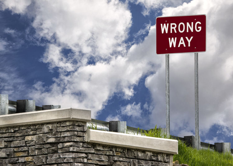 Wrong way sign at highway exit ramp. Bad Condition Copy Space Sign Traffic Problem Cloud - Sky Danger Exit Ramps Failure  Interstate Highway Mistake No People Outdoors Road Warning Sign Traffic Violation Warning Sign Wrong Way