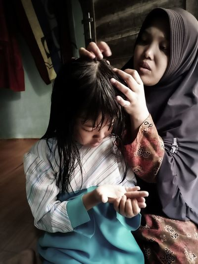 Woman cleaning daughter hair