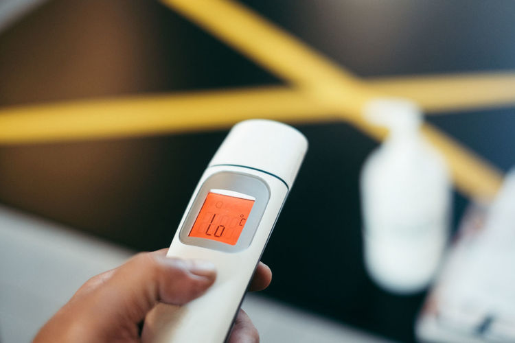 Cropped hand of person holding infrared thermometer