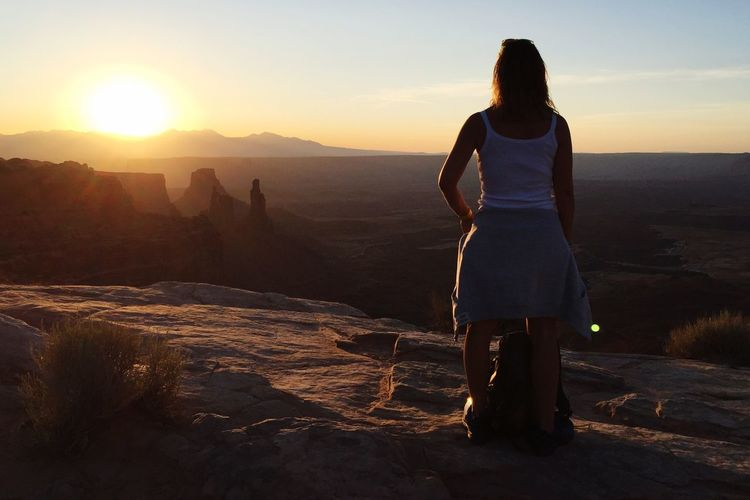 Rear view of woman standing on rock at sunset