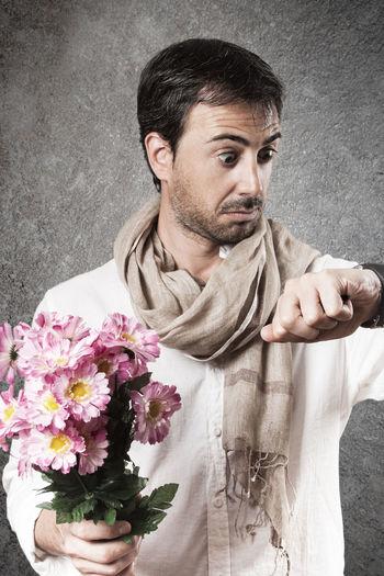 Portrait of young man holding flower bouquet