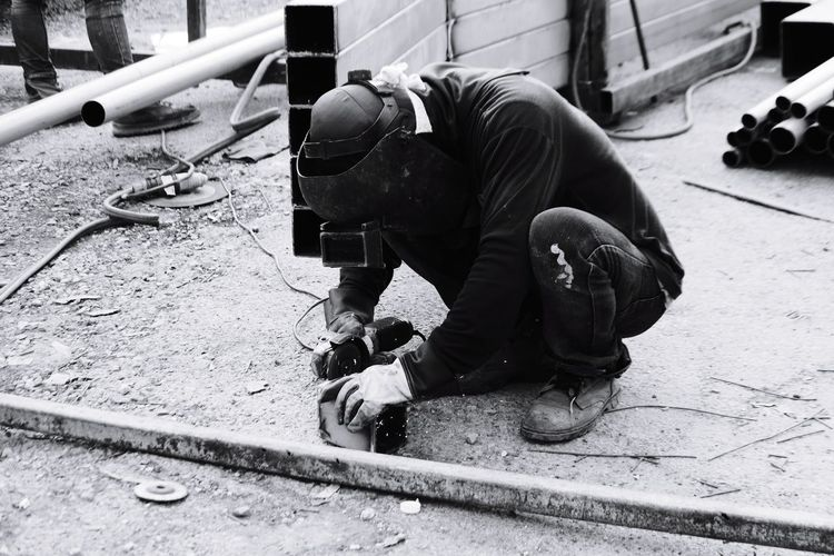 Full length of manual worker working with tool on land