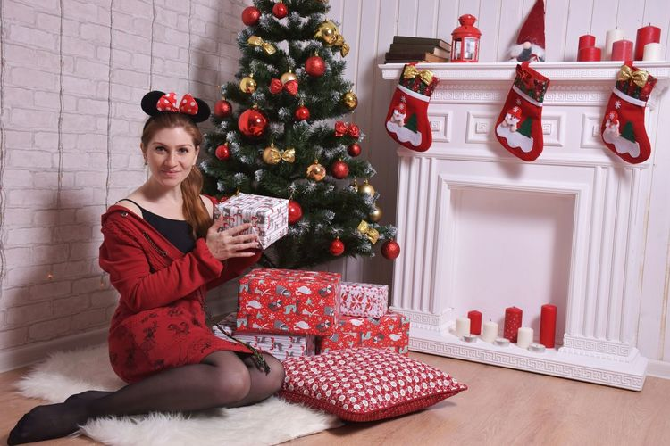 Portrait of young woman holding gift box by christmas tree at home