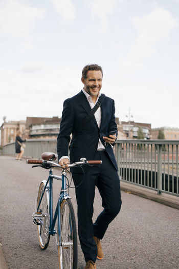 Full length of a smiling man with bicycle in city