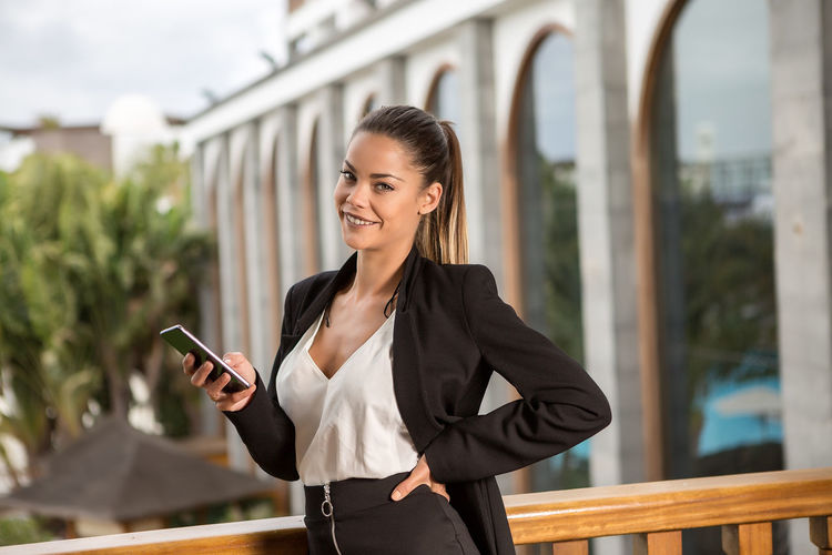 Beautiful smiling woman in elegant suit standing on balcony with smartphone and looking at camera on urban background Beautiful Content Elegant Lady Positive Standing Terrace Woman Cheerful Confident  Connection Formal Hand On Waist Holding Network Outdoors Phone Professional Smartphone Success Technology Using Laptop Wireless Technology Women Young Adult