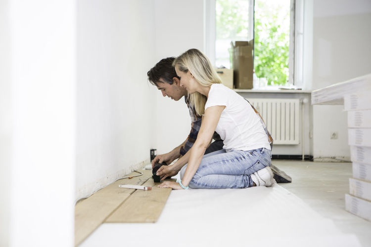 Side View Of Couple Doing Carpentry Work At Home