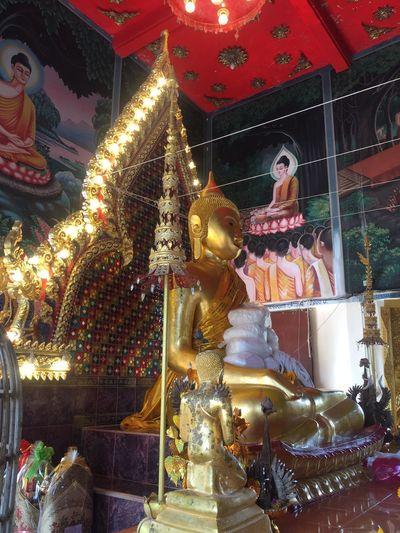 Statue against illuminated building at temple
