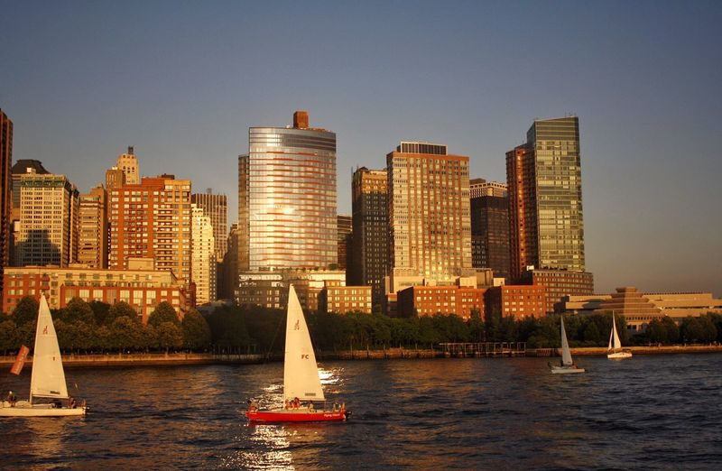 Sailboats In Front Of Cityscape At Sunset
