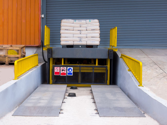 Loading dock leveler ramp outside warehouse building for loading and unloading cargo,Part of industrial or commercial building Container Entrance Industrial Logistics Transportation Architecture Cargo Day Dock Frlooring Hydraulic Industry Leveler Loading No People Outdoors Outside Pallet Ramp Storehouse Stuff Truck Unloading Vihicle Warehouse