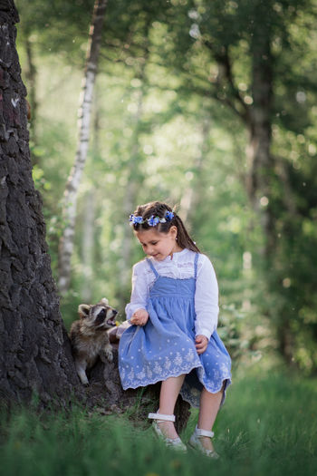 Girl sitting by raccoon at forest