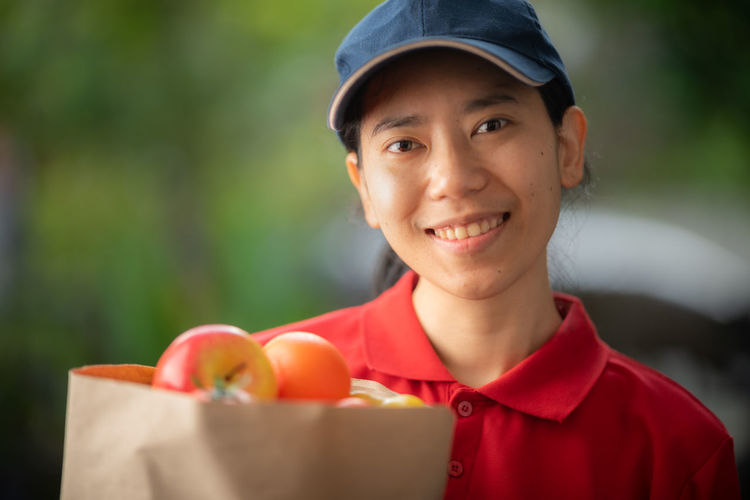 Portrait of smiling man holding strawberry outdoors
