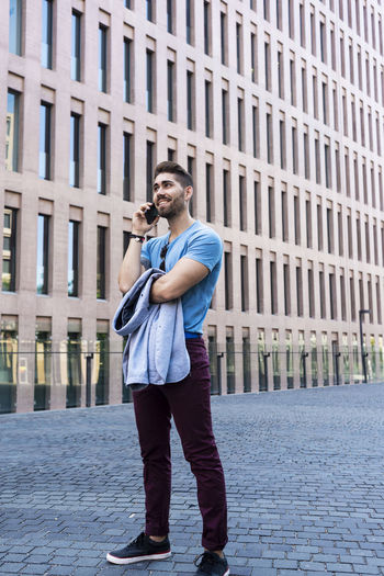 Full length of young man standing against building in city