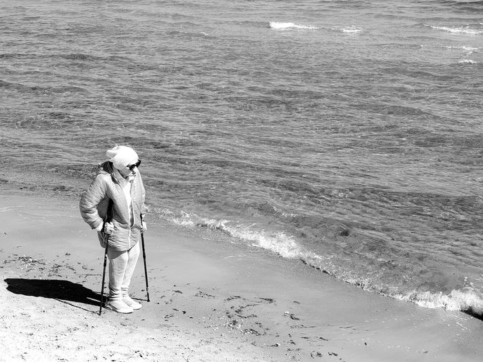 Full length of woman standing on shore at beach during sunny day