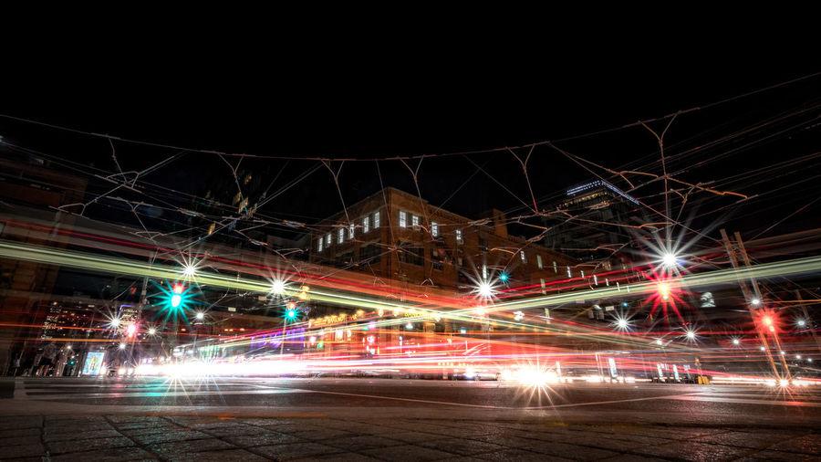Light trails on illuminated city against sky at night