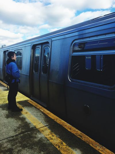 Side view of man standing by train at railroad station platform
