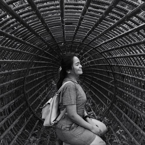 Smiling woman kneeling in metallic structure