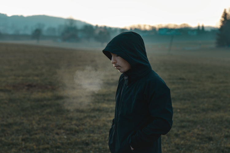 thinking teen with hoodie standing outside at field and breathe out Breathe Out Breathing Field Exhausted Tired Outside Nature Land Hoodie Leisure Activity Cold Side View Standing Outdoors Environment Lifestyles Teen Youth Young Alone Winter My Best Photo