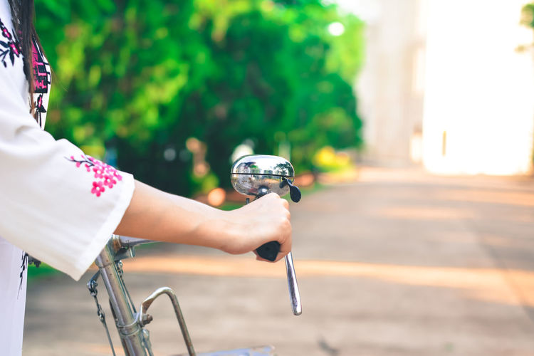 Cropped Hand Of Woman Holding Bicycle Handle Outdoors