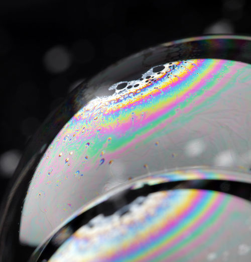 Closeup of soap bubbles. The iridescent colours of soap bubbles are caused by interfering of (internally and externally) reflected light waves and are determined by the thickness of the film.